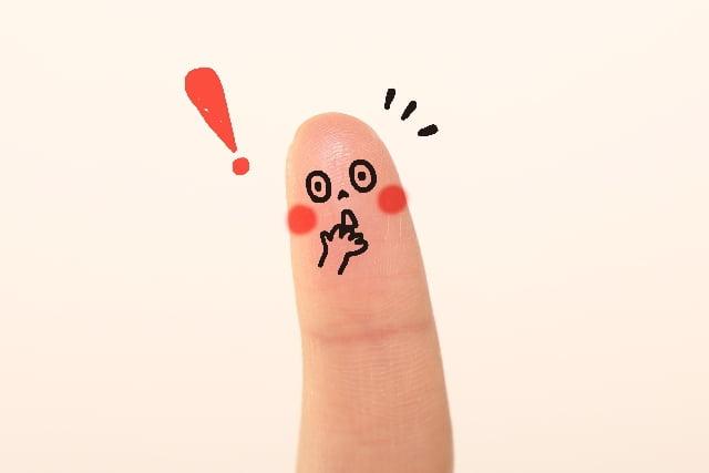 顔の書かれた指とビックリマーク